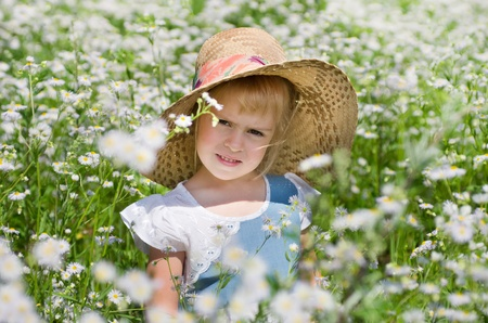 The little girl in a straw hat among the daisies