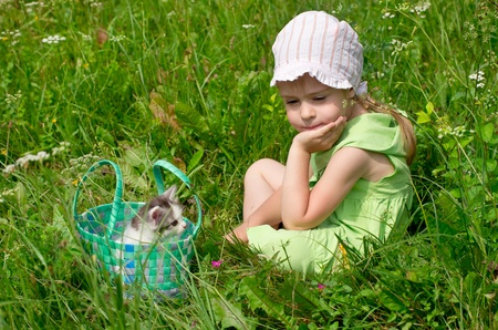 A little girl with the kitten for a walk on the lawn