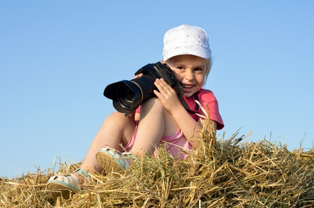 season photos: Little girl sitting on straw with a camera Stock Photo