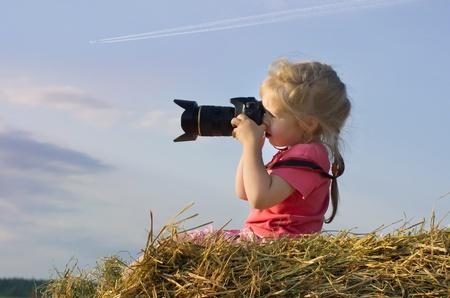 Kleines Mädchen sitzt auf einem Haufen Heu und Sonnenuntergang Fotos
