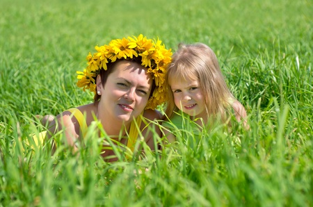 Mom and baby daughter are in the high green grass Stock Photo - 10702656