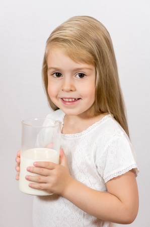 Cheerful girl holding a large glass of milk. Breakfast time.