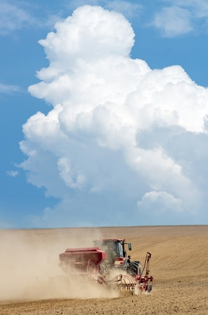 seed drill: Tractor working in the field. Time of sowing.  Stock Photo