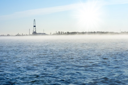Lake frosty morning with the oil field in the background. Steam over the water from the low temperature photo