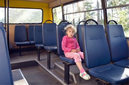 A girl in a bus. Little sad girl a riding on the bus, looking out the window photo