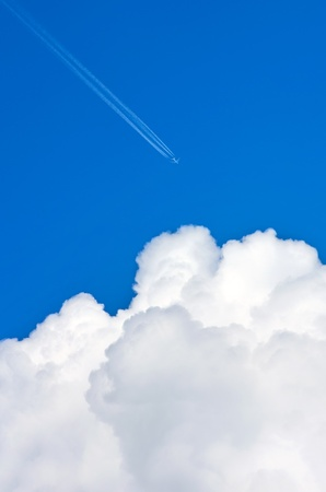 The plane comes in the blue sky beyond the clouds photo