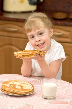 Cheerful girl holding a delicious pancake photo