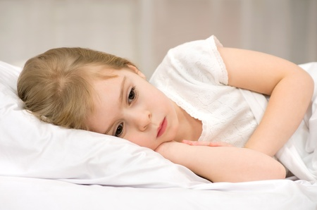 Die traurige kleine Mädchen im Bett liegend Lizenzfreie Bilder