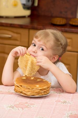 Das kleine Mädchen ist nackt hinter einem Tisch auf Küche