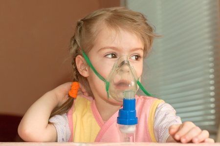 inhalation: A little girl three years doing inhalation  Stock Photo