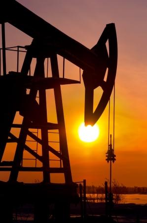 yacimiento petrolero: Bomba de aceite rockero cerca de la salida del sol de fondo
