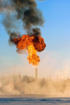 evaporacion: La quema de gas asociado en la producción de petróleo. Pares de la nieve alrededor de la antorcha. Foto de archivo