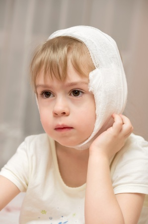 Little girl with a compress on the sore ear photo