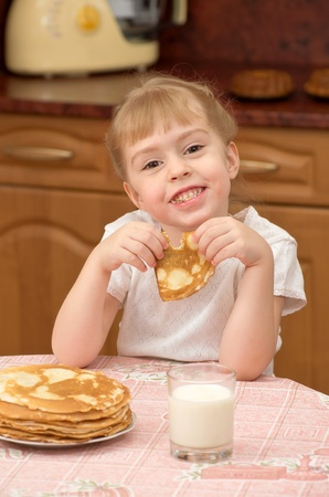 Funny little girl eats pancakes photo