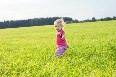 The little girl runs across the field on a decline
