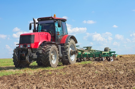 Tractor with cultivator handles field before planting photo