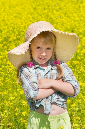 The little girl in the hat among the blossoming of the field. photo