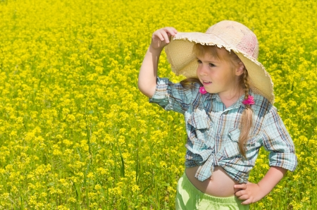 The little girl in the hat among the blossoming of the field. The child looks into the distance. photo
