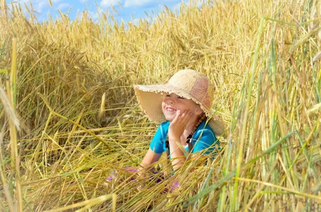 Funny girl sits among the tall rye. photo