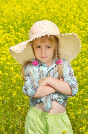 mustard field: The sad little girl among a blossoming field