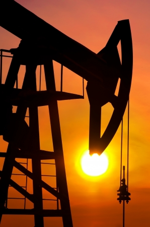 oilfield: Oil pump rocker close to sunrise background