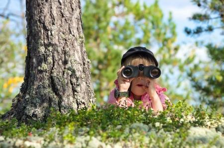 campamento: Niña mirando a través de binoculares con una cara de sorpresa