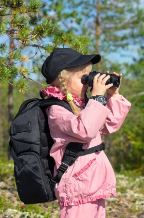 Little girl in a forest looking through binoculars photo