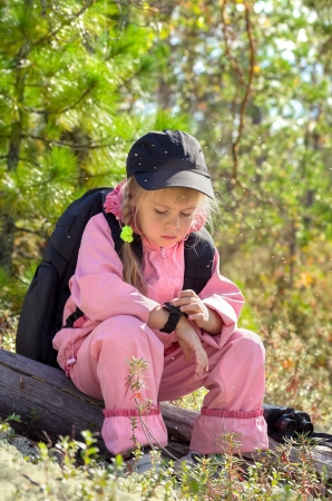 Midges in the Siberian taiga. The child looks at the compass. Stock Photo - 14934847