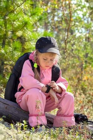 petite fille triste: Moucherons dans la taïga sibérienne. L'enfant regarde la boussole.