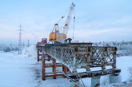 The cost of removing the old bridge on a winter evening photo