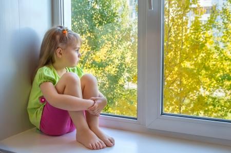 view window: Sad girl in the window