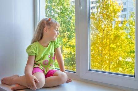 Fröhlich Mädchen sitzt am Fenster