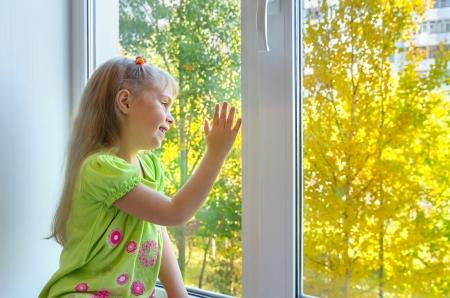 窓のそばに座っている陽気な女の子 写真素材