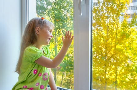 look through window: Cheerful girl sitting by the window Stock Photo