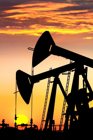 well platform: Silhouettes of oil pumps at dawn sky background