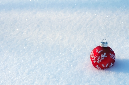 snow drift: Red Christmas ball on a snowy background.