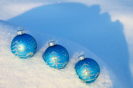 Three blue Christmas balls lying on the snow drifts photo