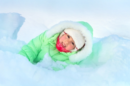 Cheerful girl lying in deep snow drift Stock Photo - 17057950