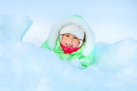 Cheerful girl lying in deep snow drift Stock Photo - 17061326