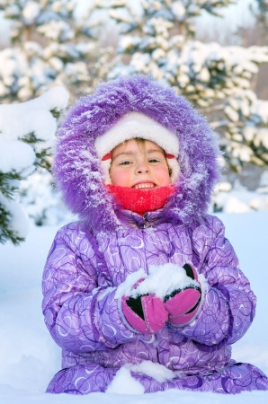 Cheerful little girl playing in a snowy forest Stock Photo - 17076395
