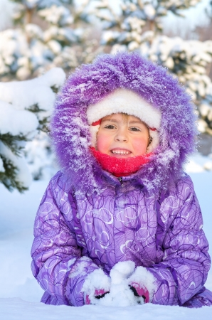 Cheerful little girl playing in a snowy forest Stock Photo - 17076415