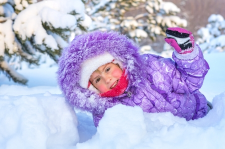 Cheerful little girl playing in a snowy forest  On the face of snowflakes and a drop of water from melting snow  Stock Photo - 17076416