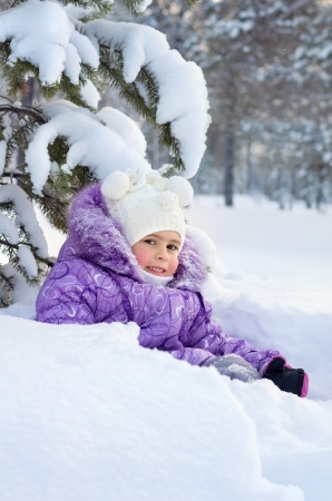 Little girl sits under snow covered branches in the deep snow Stock Photo - 17108955