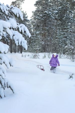 Little girl walking in winter forest