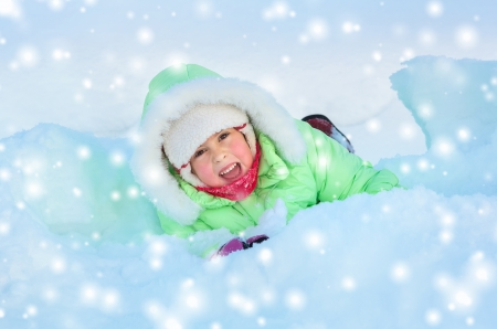 snow drift: Cheerful girl lying in deep snow drift