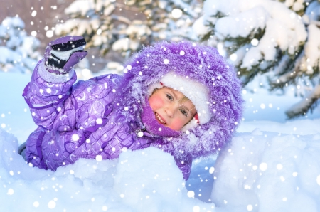 Cheerful little girl playing in a snowy forest  On the face of snowflakes and a drop of water from melting snow Stock Photo - 17279683