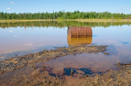 Roestig barrel en sporen van de goot olie in het meer Stockfoto