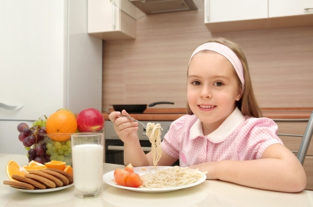 Cheerful little girl eats in the kitchen photo