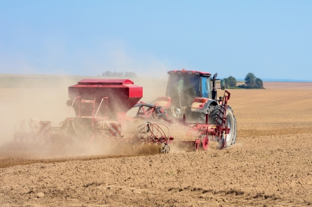 Tractor working in the field. Time of sowing.  Stock Photo