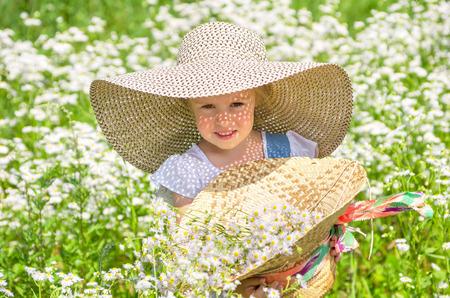 chapeau de paille: Petite fille marchant sur le terrain avec les marguerites Banque d'images
